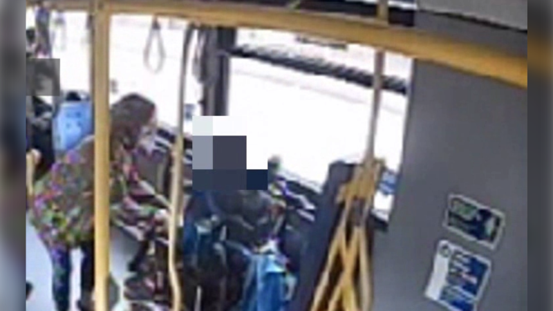 Surveillance video from the bus shows the woman grabbing the man's phone, which he is holding in his lap. (Metro Vancouver Transit Police)