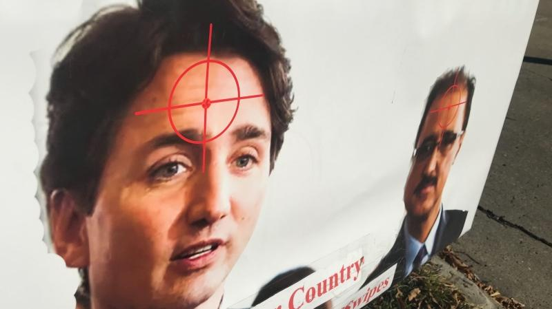 A sign depicts Liberal Leader Justin Trudeau and Edmonton Mill Woods Liberal candidate Amarjeet Sohi with crosshairs on their foreheads. Oct. 3, 2019. (CTV News Edmonton)