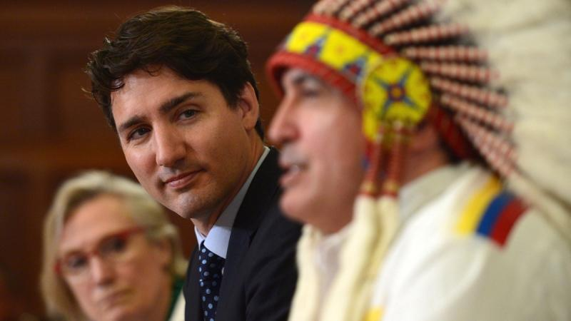 Minister of Indigenous and Northern Affairs Carolyn Bennett, left, looks on as Prime Minister Justin Trudeau and Assembly of First Nations Chief Perry Bellegarde participates in the signing of the Assembly of First Nations-Canada Memorandum of Understanding on Joint Priorities on Parliament Hill, on June 12, 2017. (THE CANADIAN PRESS / Sean Kilpatrick)