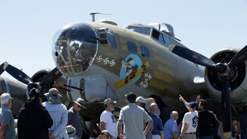 In this photo taken June 2, 2018 photo, people look over the Nine-O-Nine, a Collings Foundation B-17 Flying Fortress, at McClellan Airport in Sacramento, Calif. A B-17 vintage World War II-era bomber plane crashed Wednesday, Oct. 2, 2019, just outside New England's second-busiest airport, raising questions on the safety of continuing to fly vintage aircraft. (AP Photo/Rich Pedroncelli)