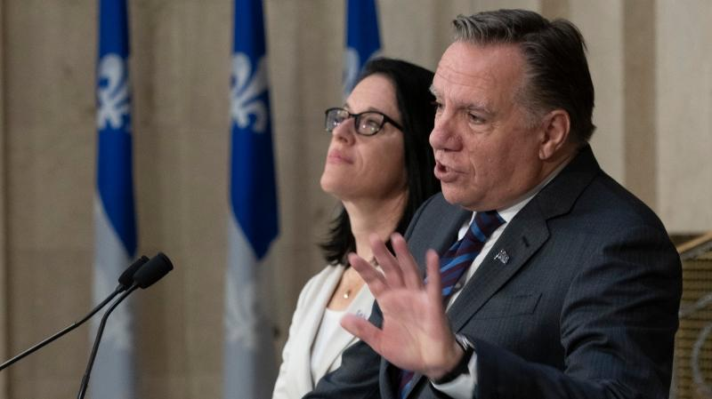 Quebec Premier Francois Legault reacts to the election of a Liberal minority government at the National Assembly in Quebec City, Tuesday, Oct. 22, 2019. Quebec Justice Minister and Minister Responsible for Canadian Relations and the Canadian Francophonie Sonia Lebel, left, looks on. THE CANADIAN PRESS/Jacques Boissinot