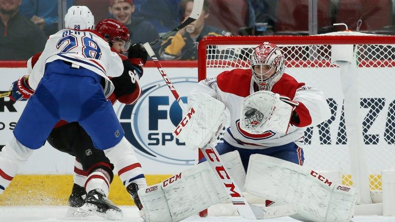 Montreal Canadiens goaltender Carey Price, right, makes a glove save on a shot as Canadiens defenseman Mike Reilly (28) clears Arizona Coyotes right wing Conor Garland, second from left, away from the goalie during the second period of an NHL hockey game Wednesday, Oct. 30, 2019, in Glendale, Ariz. (AP Photo/Ross D. Franklin)