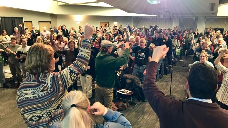 "The crowd raises their fists in solidarity at a ""Resist Kenney's Cuts"" meeting on Dec. 2, 2019."