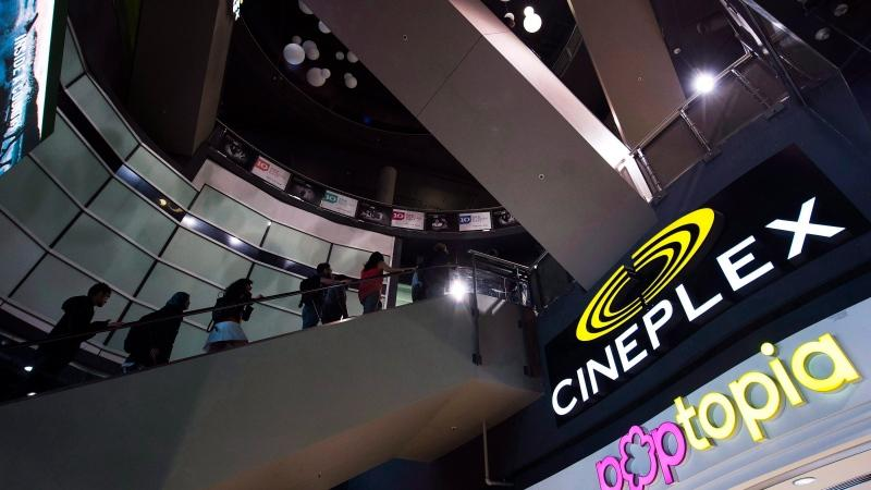 People make their way an escalator at the Cineplex Entertainment company's annual general meeting in Toronto on May 17, 2017. (Nathan Denette/THE CANADIAN PRESS)