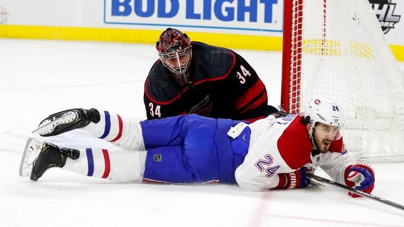 Montreal Canadiens' Phillip Danault (24) slides on the ice past Carolina Hurricanes goaltender Petr Mrazek (34), of the Czech Republic, during the first period of an NHL hockey game in Raleigh, N.C., Tuesday, Dec. 31, 2019. (AP Photo/Karl B DeBlaker)