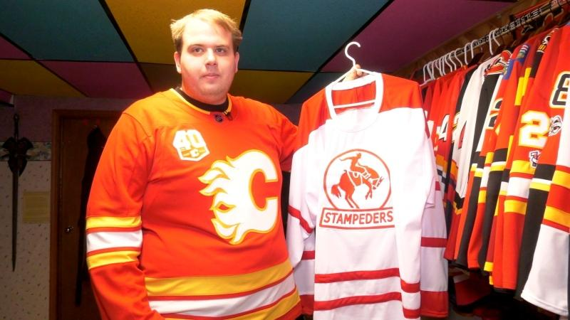 Chris Wilson of Canmore holds up a jersey of the Stampeders, a Calgary men's professional hockey team that existed decades before the Calgary Flames franchise known today. It's part of his 40-jersey collection that includes Team Canada hockey sweaters and others from the Heritage Classic series.