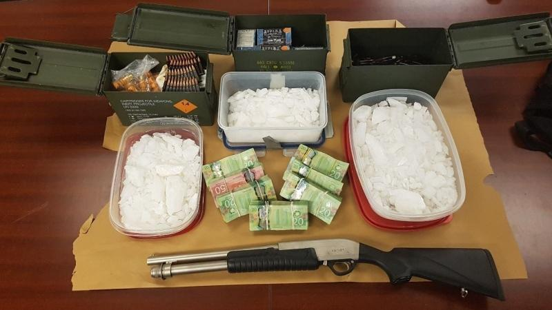A shotgun, drugs and cash seized from two locations in London, Ont. are seen in this London Police Service image.