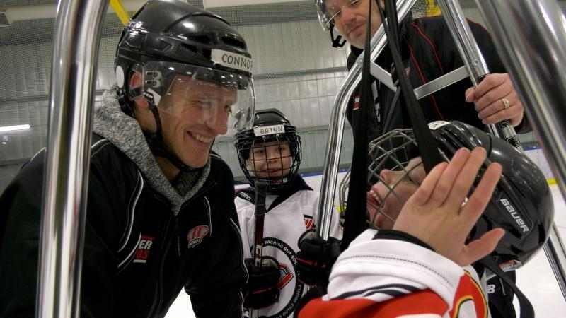 Piper (right) smiles at one of her coaches as her big sister Brynn (centre) cheers her on. Piper was born with cerebral palsy and played ice hockey for the first time ever on Sunday, thanks to the metal bars of a unique apparatus acquired by her hockey team.