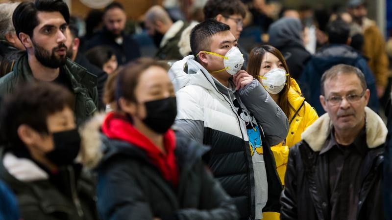 "People wear masks as they wait for the arrivals at the International terminal at Toronto Pearson International Airport in Toronto on Saturday, January 25, 2020. Two professors are warning that ""coronaphobia"" could be spurring on xenophobia in Canada. THE CANADIAN PRESS/Nathan Denette"