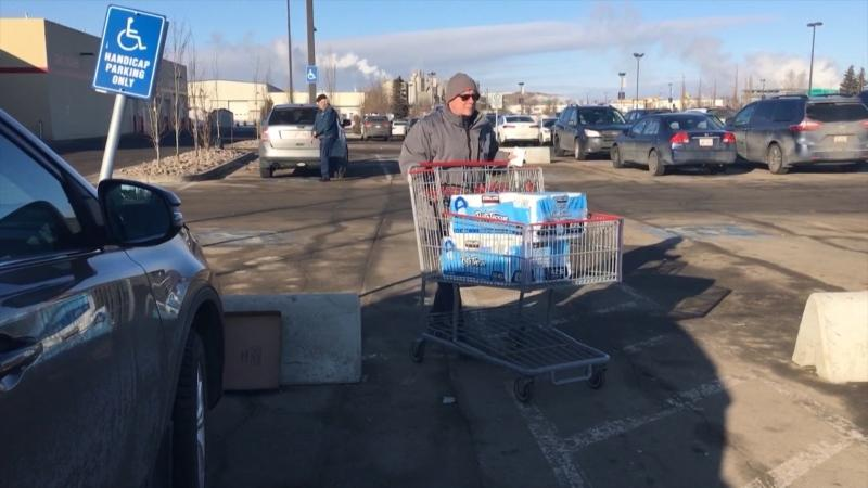 A man pushes a cart filled with toilet paper outside a Costco on March 5, 2020.