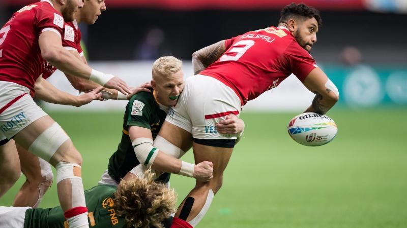 Canada's Mike Fuailefau, right, looks to pass while being tackled by South Africa's Ryan Oosthuizen, centre, and Werner Kok, bottom left, during the bronze medal match at the Canada Sevens rugby tournament in Vancouver, on Sunday, March 8, 2020. THE CANADIAN PRESS/Darryl Dyck