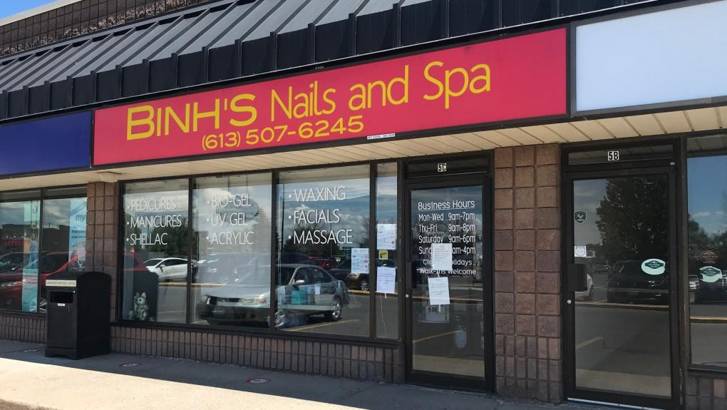A sign on the door of Binh's Nails and Spa in Kingston says a customer tested positive for COVID-19. (Kimberley Johnson/CTV News)