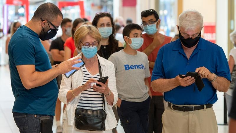 Shoppers wear masks as they line up at a mall in Laval, Que. THE CANADIAN PRESS/Ryan Remiorz