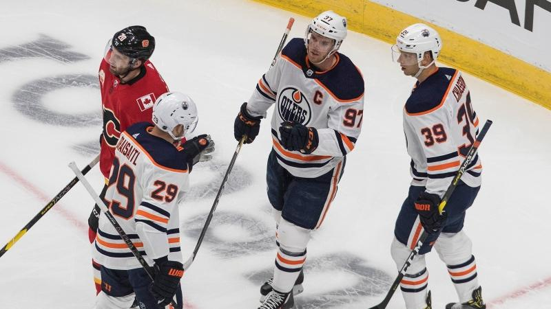 Edmonton Oilers' Leon Draisaitl (29), Connor McDavid (97) and Alex Chiasson (39) celebrate a goal as Calgary Flames' Derek Forbort (20) skates by during first period NHL exhibition game action in Edmonton on Tuesday, July 28, 2020. THE CANADIAN PRESS/Jason Franson