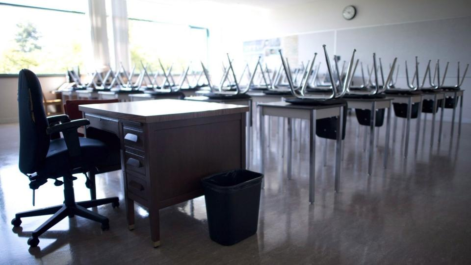 An empty teacher's desk is seen at the front of a empty classroom. (THE CANADIAN PRESS/Jonathan Hayward)