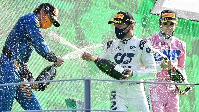 Race winner AlfaTauri driver Pierre Gasly of France, centre, sprays champagne on the podium with second placed Mclaren driver Carlos Sainz of Spain, left, and third placed Racing Point driver Lance Stroll of Canada after the Formula One Grand Prix at the Monza racetrack in Monza, Italy, Sunday, Sept. 6, 2020. (Miguel Medina, Pool via AP)