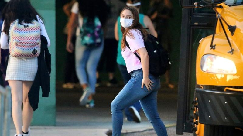 A student arrives by bus on the first day of school before the start of classes at the entrance of Gulf High School on Monday, Aug. 24, 2020, in New Port Richey, Fla. (Douglas R. Clifford/Tampa Bay Times via AP)