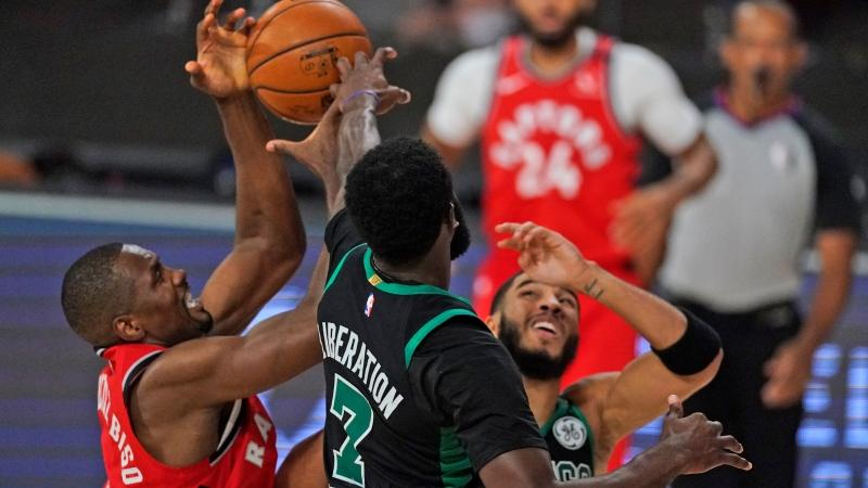 Toronto Raptors' Serge Ibaka, left, battles for the ball with Boston Celtics' Jaylen Brown (7) and Boston Celtics' Jayson Tatum, right, during the first half of an NBA conference semifinal playoff basketball game Monday, Sept. 7, 2020, in Lake Buena Vista, Fla. (AP Photo/Mark J. Terrill)