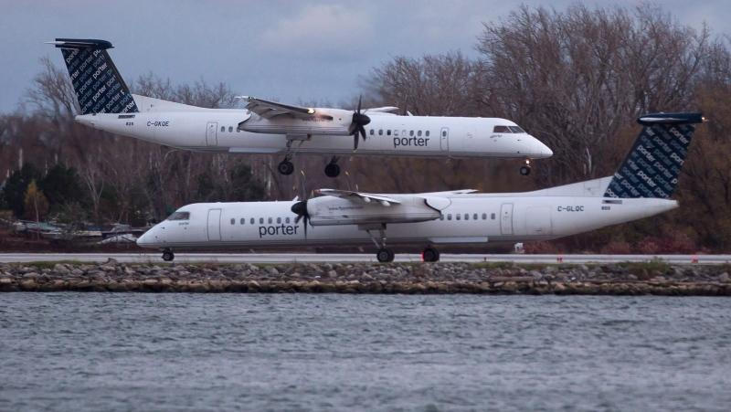 A Porter Airlines plane lands next to a taxiing plane at Toronto's Island Airport on Friday, November 13, 2015. Aimia and Porter regional airline form new Aeroplan partnership to become effective July 2020, after Aimia's partnership with Air Canada ends.THE CANADIAN PRESS/Chris Young