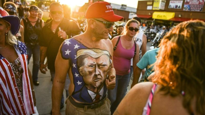A man walks down Main Street in Sturgis, S.D., showing off his chest painted with a portrait of U.S. President Donald Trump during the 80th Annual Sturgis Motorcycle Rally on Aug. 7, 2020. (AFP)