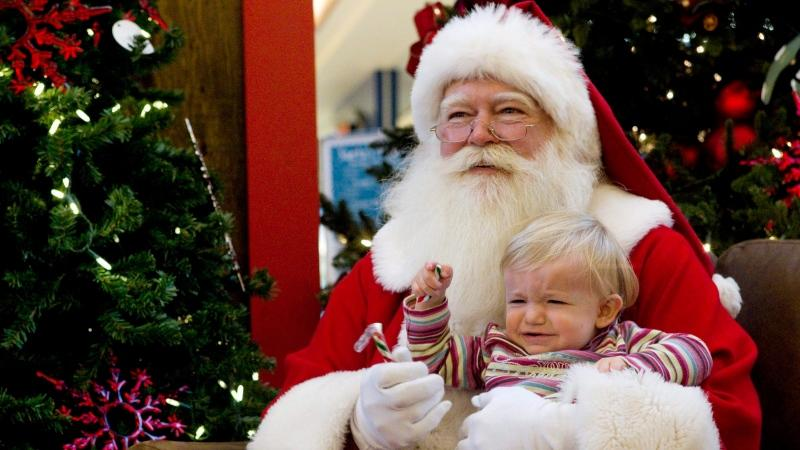 Seventeen-month-old Siria Pirone reacts as she sits with a Santa Claus for a photo at a mall in Toronto on Friday December 10, 2010. THE CANADIAN PRESS/Chris Young