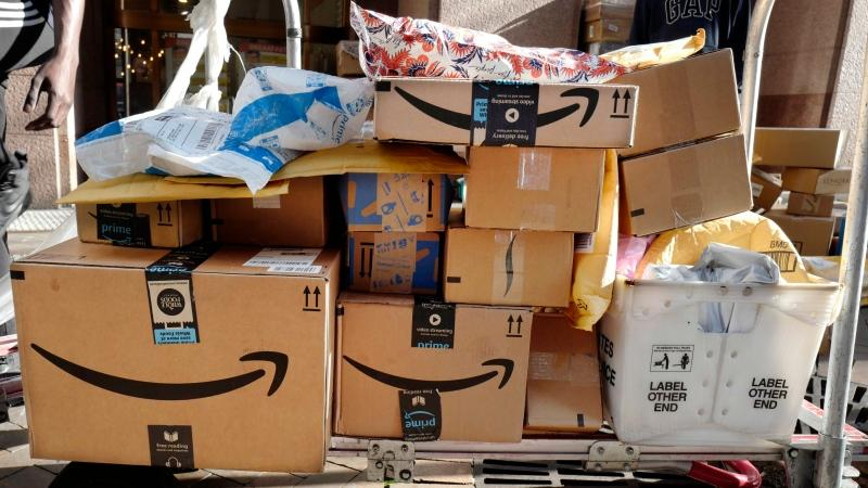 In this Oct. 10, 2018, file photo Amazon Prime boxes are loaded on a cart for delivery in New York. The increase of online shopping has added to the increase of boxes stacking up at people's homes. (AP Photo/Mark Lennihan, File)