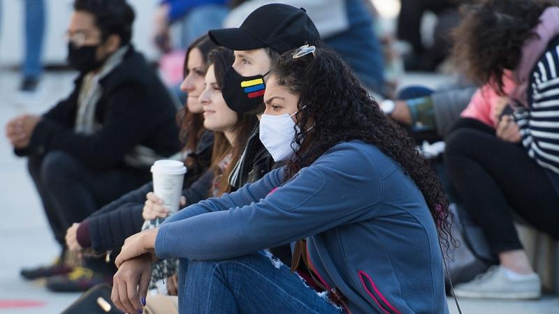 People wear face masks as they attend an outdoor event in Montreal, Sunday, Sept. 20, 2020, as the COVID-19 pandemic continues in Canada and around the world. THE CANADIAN PRESS/Graham Hughes