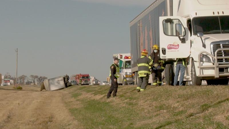 Emergency crew members speak with the driver of a semi after a wind gust separated his load and sent a trailer into the ditch on Highway 3 east of Lethbridge Tuesday morning.