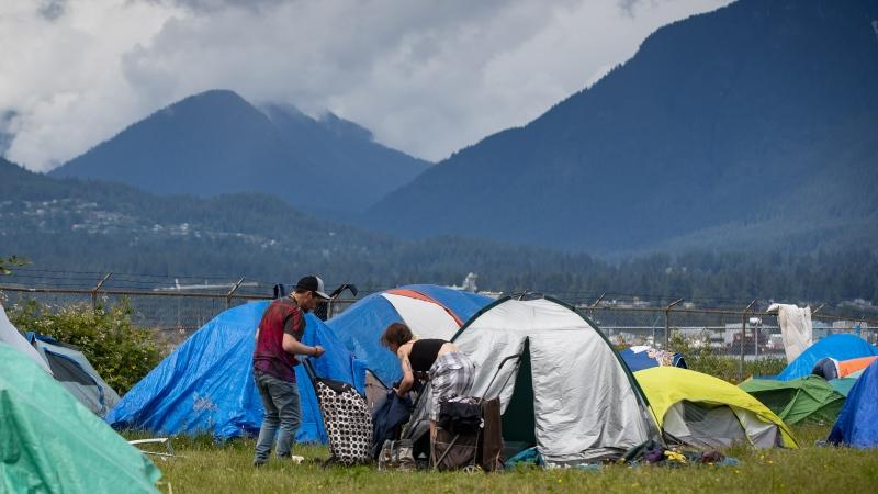 People are seen outside a tent at a homeless camp in Vancouver, Saturday, June 13, 2020. (Darryl Dyck / THE CANADIAN PRESS)