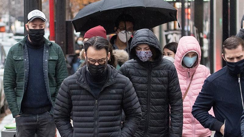 People wear face masks as they walk along a street in Montreal, Sunday, November 1, 2020, as the COVID-19 pandemic continues in Canada and around the world. THE CANADIAN PRESS/Graham Hughes