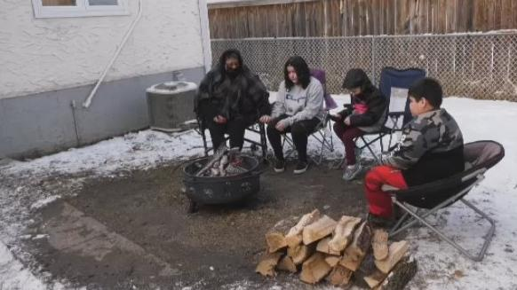 Despite a chilly wind, family members huddle around a sacred fire burning for Denise Acoby and her 8-month-old daughter London on Nov. 20, 2020. (Source: Mason DePatie/CTV News Winnipeg)