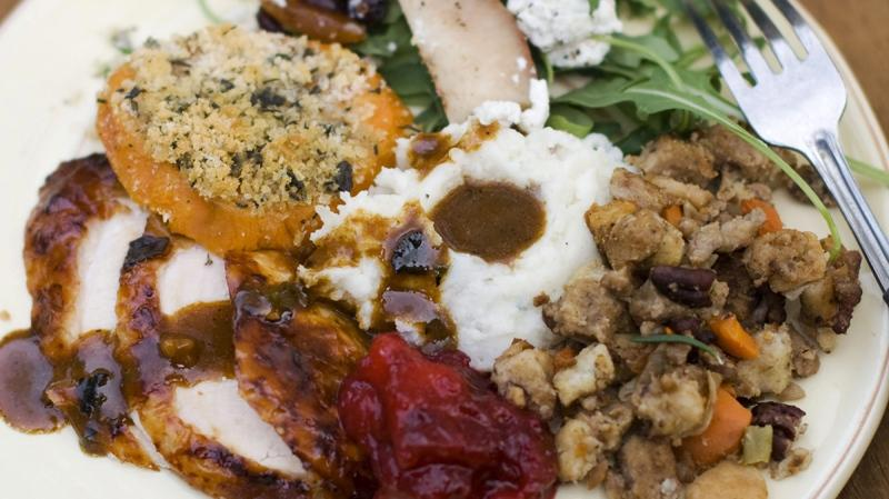 A dinner plate of cider-brined turkey with sage gravy, peach cranberry sauce, sour cream and chive mashed potatoes, sausage pecan stuffing, arugula pear salad with pomegranate vinaigrette and goat cheese and herb crusted sweet potatoes is shown in Concord, N.H. (AP /Matthew Mead)