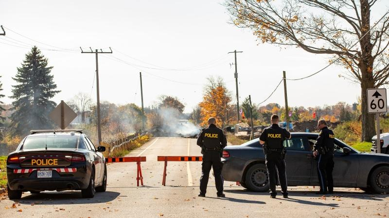 Ontario Provincial Police are shown at a blockade on McKenzie Rd. in Caledonia, Ont., on Friday, Oct.23, 2020, after a judge granted a permanent injunction against a land reclamation camp known as 1492 Land Back Lane. THE CANADIAN PRESS/Tara Walton