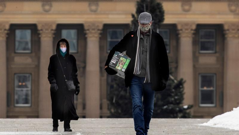 Pedestrians wears masks while out walking in front of the Alberta Legislature as the COVID-19 numbers spike in Edmonton on Tuesday November 24, 2020. THE CANADIAN PRESS/Jason Franson