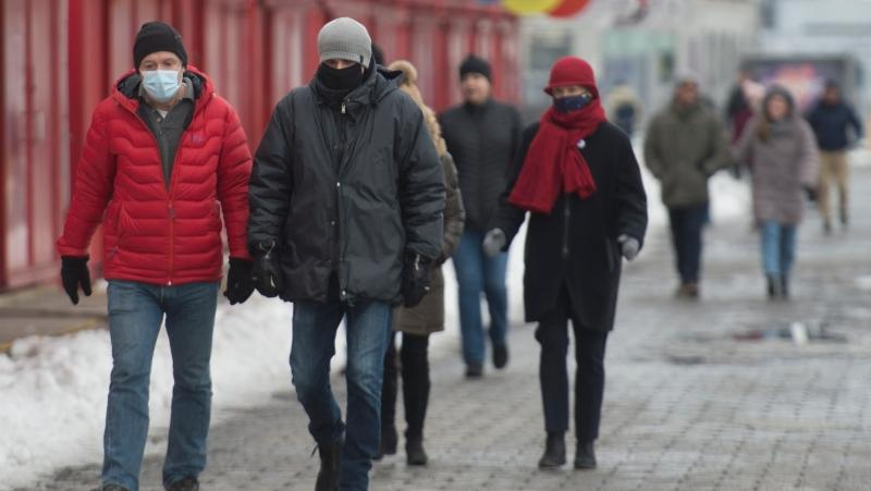 People wear face masks as they walk in the Old Port in Montreal, Friday, January 1, 2021, as the COVID-19 pandemic continues in Canada and around the world. THE CANADIAN PRESS/Graham Hughes