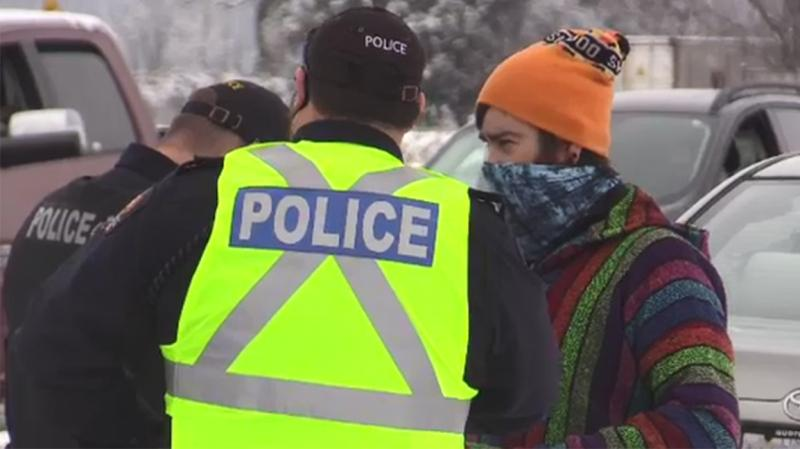 Police speak with a protestor who entered Church of God property in Aylmer, Ont. on Jan. 3, 2021. (Brent Lale/CTV London)