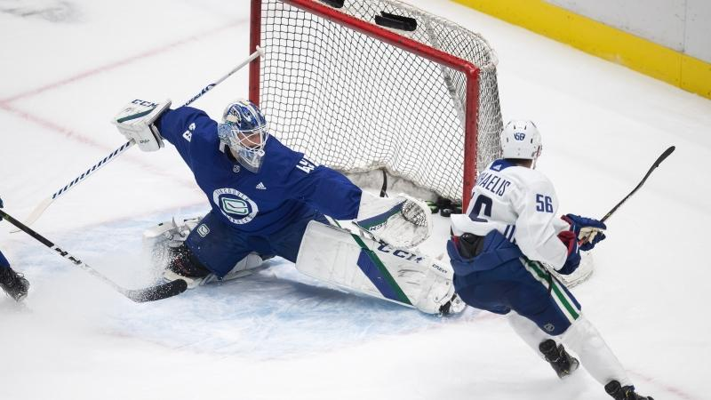 Vancouver Canucks' Marc Michaelis, right, scores against goalie Braden Holtby during the NHL hockey team's training camp in Vancouver, on Tuesday, Jan. 5, 2021. (Darryl Dyck / THE CANADIAN PRESS)
