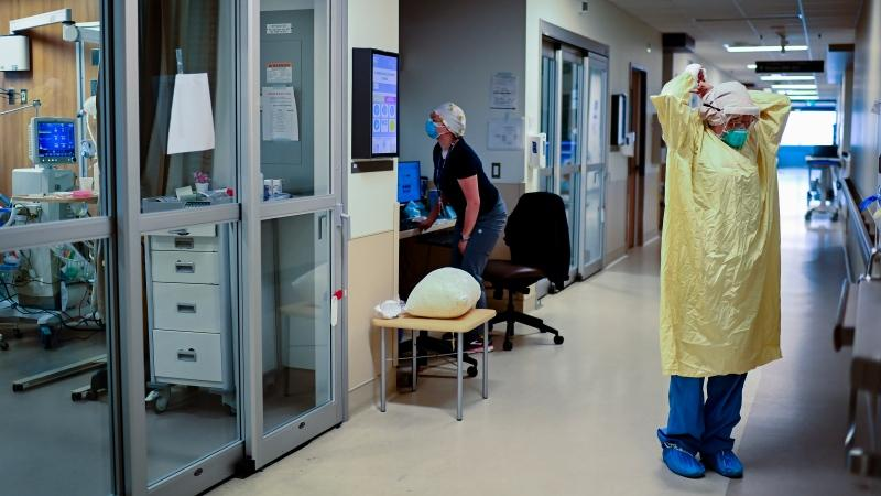 ICU health-care worker Jannikka Navaratnam suits up in PPE before entering a negative pressure room to care for a COVID-19 patient on a ventilator at the Humber River Hospital during the COVID-19 pandemic in Toronto on Wednesday, December 9, 2020. THE CANADIAN PRESS/Nathan Denette