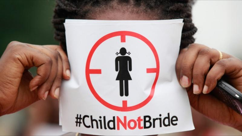 FILE - In this photo taken on Saturday, July 20, 2013, a woman protests against underage marriages in Lagos, Nigeria. (AP Photo/Sunday Alamba)
