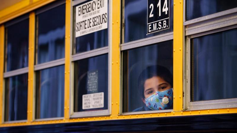A student peers through the window of a school bus as he arrives at the Bancroft Elementary School in Montreal, on Monday, August 31, 2020. THE CANADIAN PRESS/Paul Chiasson