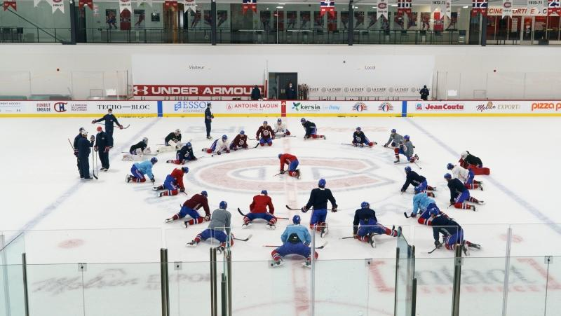 Montreal Canadiens players stretch at centre ice at their training facility during a practice in Brossard, Que. on Tuesday, January 5, 2021. THE CANADIAN PRESS/Paul Chiasson