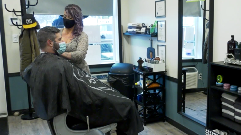 Natalie Klein, co-owner of Bladez 2 Fadez in Innisfail, Alta., serves a client in the barbershop on Jan. 12