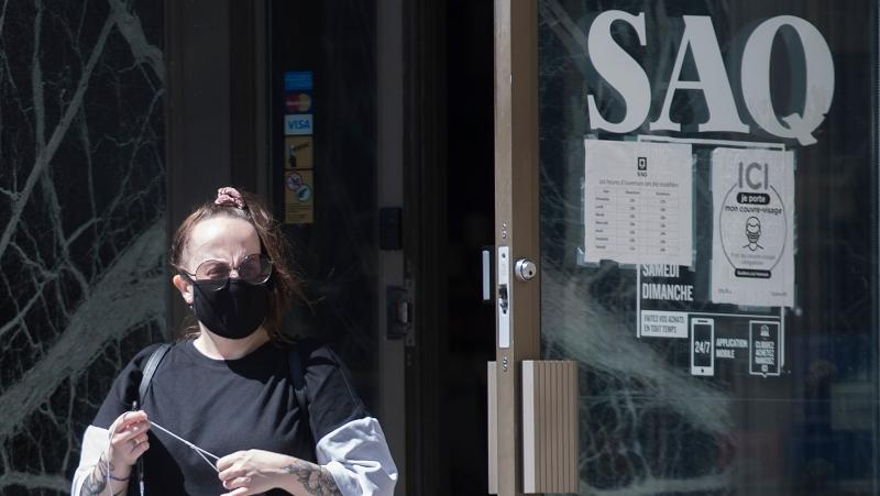A woman wears a face mask as she leaves a SAQ outlet in Montreal. Next week, only in-store sales will be available as the SAQ updates its site. THE CANADIAN PRESS/Graham Hughes