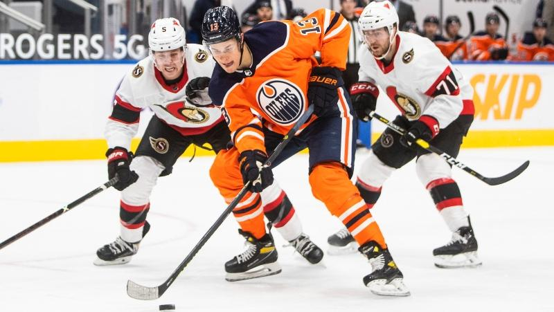 Edmonton Oilers' Jesse Puljujarvi (13) is chased by Ottawa Senators' Mike Reilly (5) and Chris Tierney (71) during second period NHL action in Edmonton on Tuesday, February 2, 2021. (THE CANADIAN PRESS/Jason Franson)