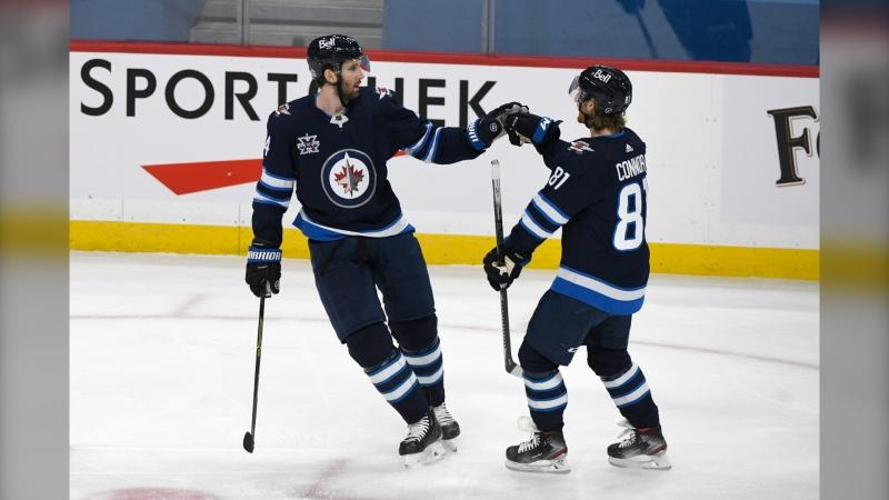Winnipeg Jets' Derek Forbort (24) celebrates his goal against the Calgary Flames with Kyle Connor (81) during first period NHL action in Winnipeg on Tuesday Feb. 2, 2021. THE CANADIAN PRESS/Fred Greenslade