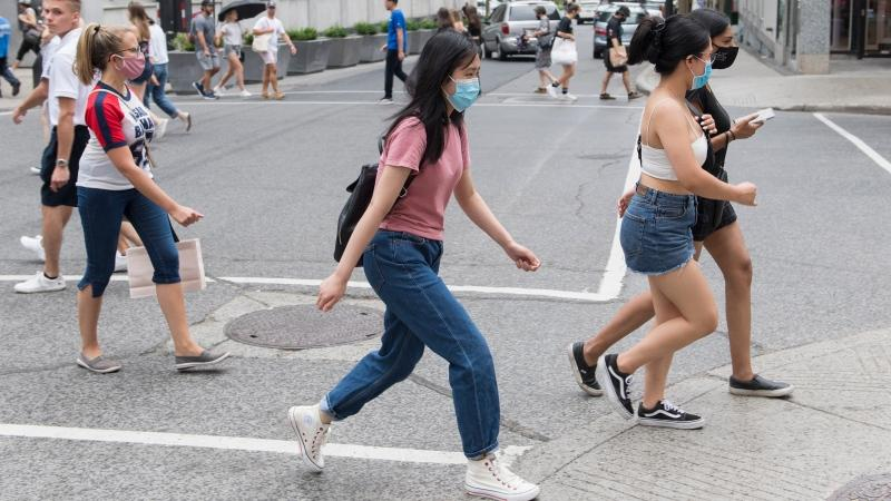 People wear face masks as they cross a street in Montreal, Sunday, August 9, 2020. THE CANADIAN PRESS/Graham Hughes