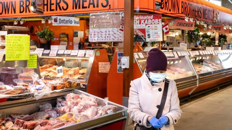 A shopper is seen in a quiet St. Lawrence Market, in Toronto, on Friday, March 20, 2020. THE CANADIAN PRESS/Chris Young