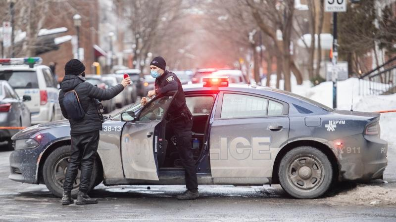 Police are shown on Durocher and Sherbrooke streets in Montreal, Sunday, February 7, 2021, where a woman fell from an apartment building and died. THE CANADIAN PRESS/Graham Hughes
