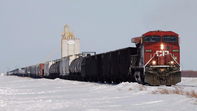 Grain and oil rail cars pass by a grain elevator in Rosser, Man., just outside Winnipeg, March 24, 2014. (THE CANADIAN PRESS/John Woods)