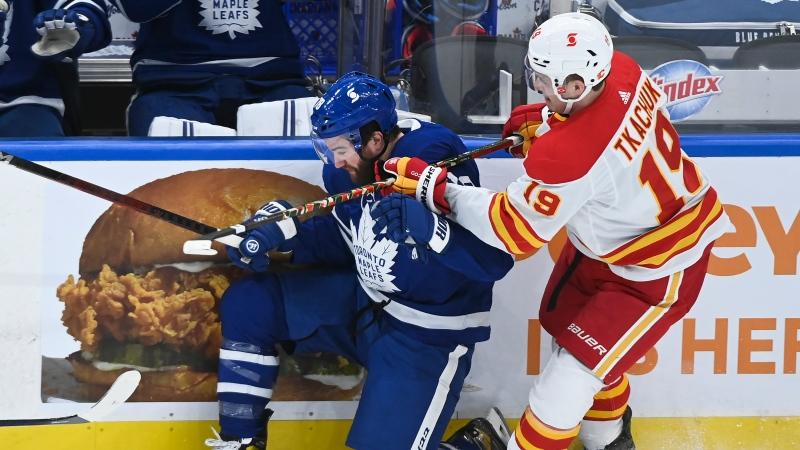 Calgary Flames left wing Matthew Tkachuk (19) takes out Toronto Maple Leafs defenceman TJ Brodie (78) during first period NHL hockey action in Toronto on Monday, February 22, 2021. THE CANADIAN PRESS/Nathan Denette